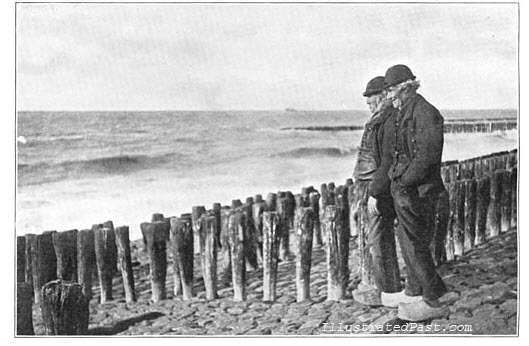 Two men look out to sea on the west coast of Holland. They are wearing Dutch clogs. The wooden stakes are to prevent erosion.