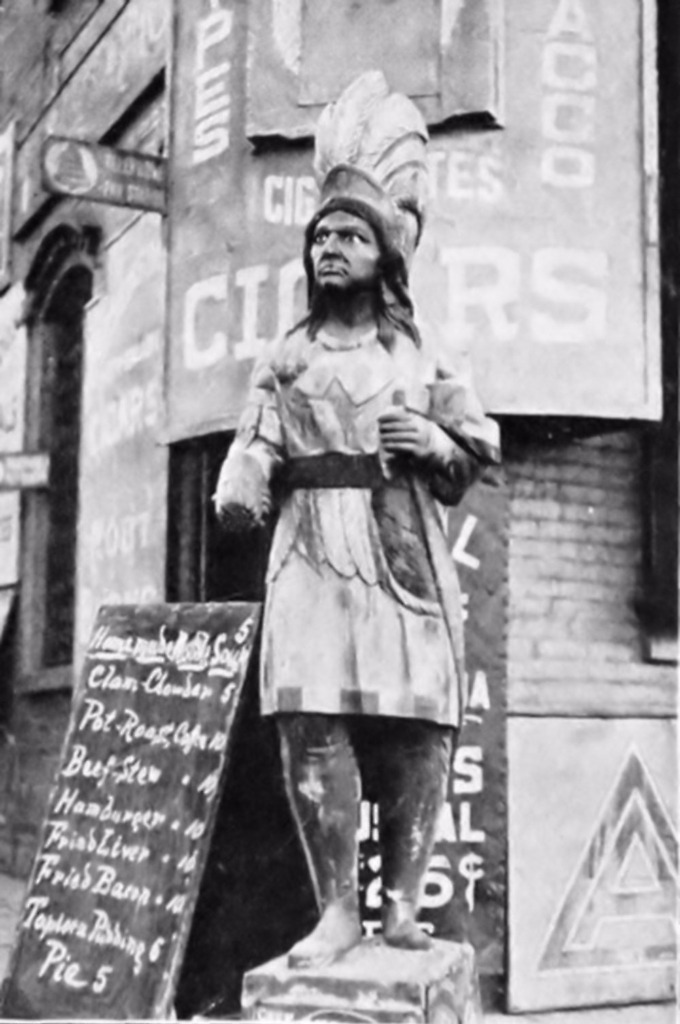 A Fearsome Cigar Store Warrior - Standing Next to a Blackboard Advertising a Restaurant Menu. The Statue is Missing a Hand.