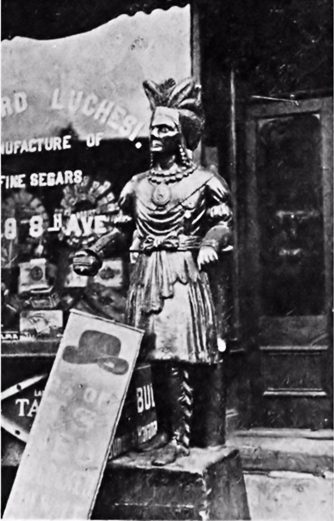 """Elaborately Carved Cigar Store Indian Stands In Front of a Shop Window Advertising Fine """"Segars""""."""